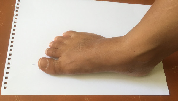 place foot for shoe size measurement on paper at home